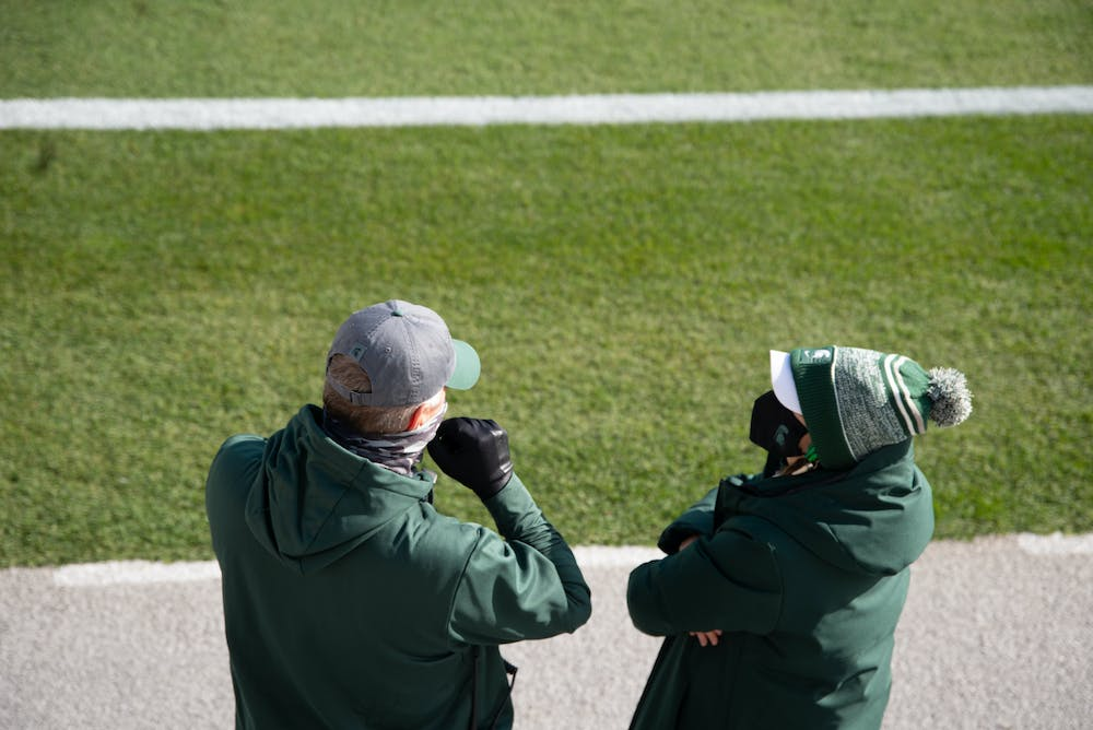 <p>Members of Spartan athletics watch the team warm up before a football game against Indiana University at Spartan Stadium on Nov. 14, 2020.</p>