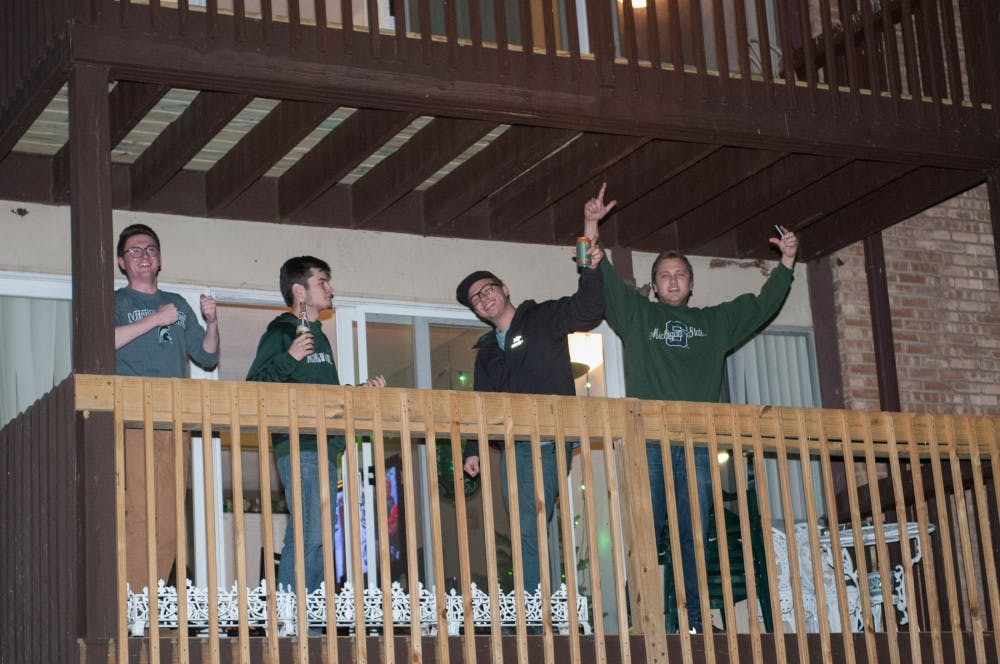 Students celebrate on the terrace after MSU's victory over Iowa on Dec. 5th, 2015, at Cedar Village.