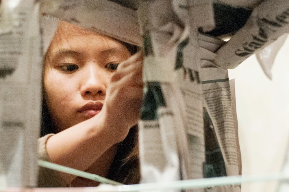 Lansing resident Huong Nguyen, 17, tapes together newspapers during a team building exercise at the Girls 2 Women conference in the Union ballroom on June 15, 2012. The conference included guest speakers and workshops about transitioning into womenhood. Julia Nagy/The State News