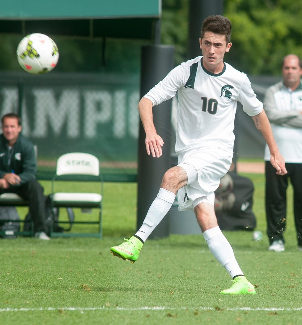 <p>Junior midfielder Jay Chapman passes the ball upfield during the game against Loyola-Chicago on Sept. 14, 2014, at DeMartin Soccer Stadium at Old College Field. Raymond Williams/The State News</p>