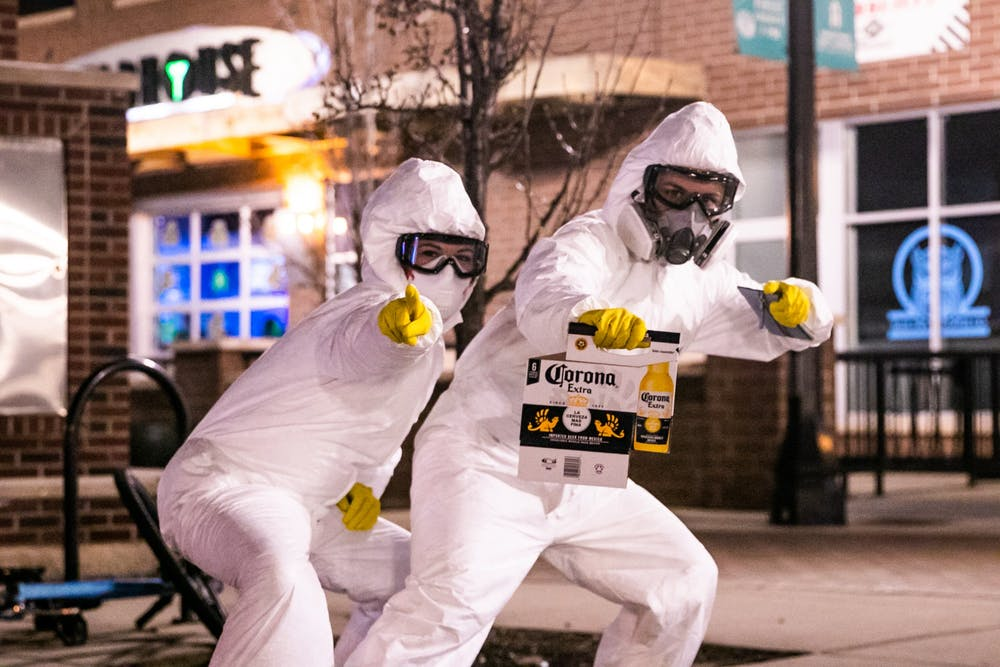 Two girls pose in hazmat suits holding an empty case of Corona in front of the bars on Albert St. after MSU cancelled classes due to coronavirus March 11, 2020.