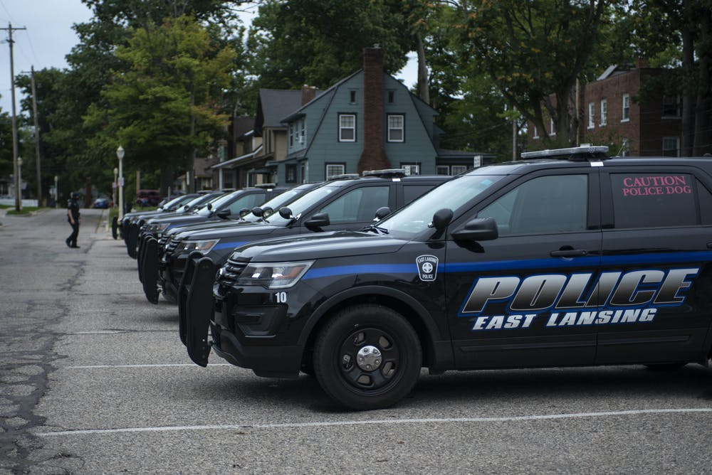 <p>A police officer walks toward the line of cars outside the East Lansing Police Department. Shot on Sept. 10, 2020.</p>