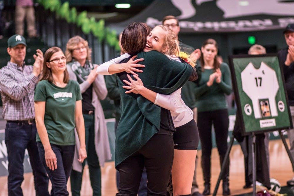Senior setter Rachel Minarick (12) hugs head coach Cathy George during the postgame senior night ceremony after the game against Indiana on November 18, 2017, at Jenison Fieldhouse. The Spartans defeated the Hoosiers, 3-0.