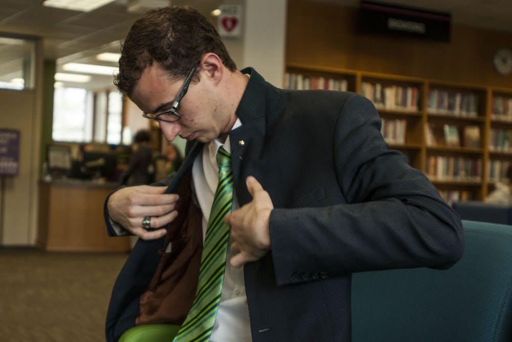 <p>President of the Associated Students of Michigan State University Lorenzo Santavicca puts on his jacket prior to walking to the Hannah Administration Building on April 24, 2018 at the Main Library. (C.J. Weiss | The State News)</p>