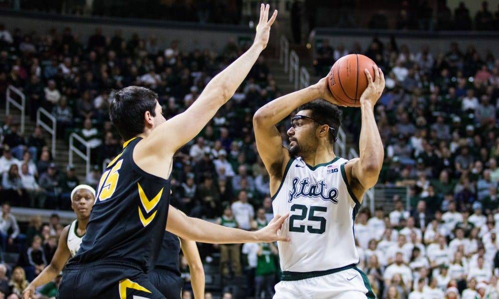 Senior forward Kenny Goins (25) looks for an open pass during the game against Iowa University at Breslin Center on Dec. 3, 2018. The Spartans defeated the Hawkeyes, 90-68.