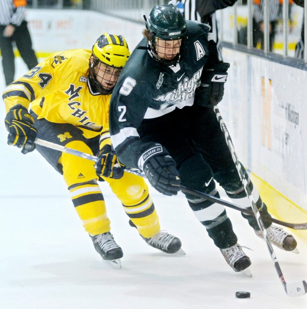 Sophomore defenseman Jeff Petry fights for control of the puck with Michigan?s Chris Summers during the second period of Saturday night?s game in Ann Arbor. MSU lost 5-3. Katie Rausch/The State News