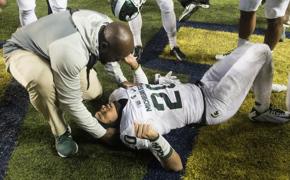 <p>Freshman defensive back Jalen Watts-Jackson lays on the ground after running the game winning touchdown on Oct. 17, 2015, after the game against Michigan at Michigan Stadium in Ann Arbor. The Spartans defeated the Wolverines, 27-23. (State News File Photo)</p>