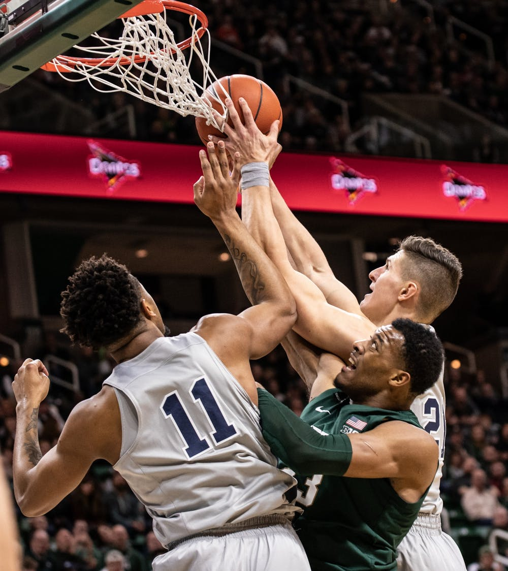 Forward Xavier Tillman fights for possession during a basketball game against Penn State at the Breslin Center on Feb. 4, 2020.