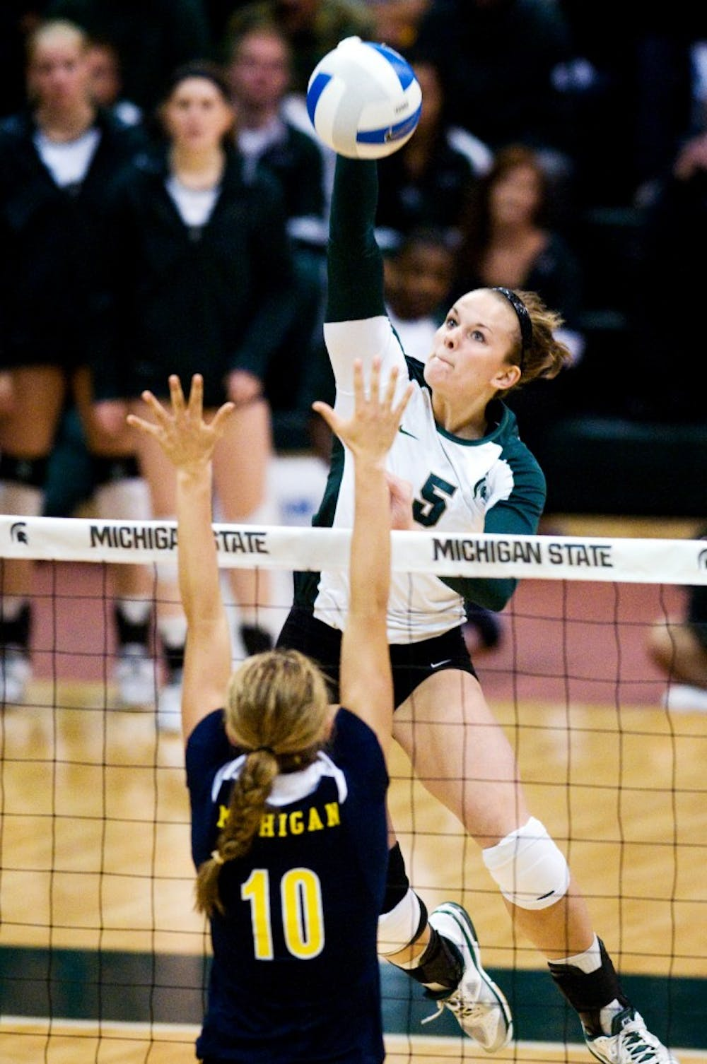 Senior outside hitter Jenilee Rathje hits the ball over Michigan setter Lexi Dannemiller Oct. 19 at Jenison Field House. The Spartans defeated the Wolverines 3-1. Matt Radick/The State News