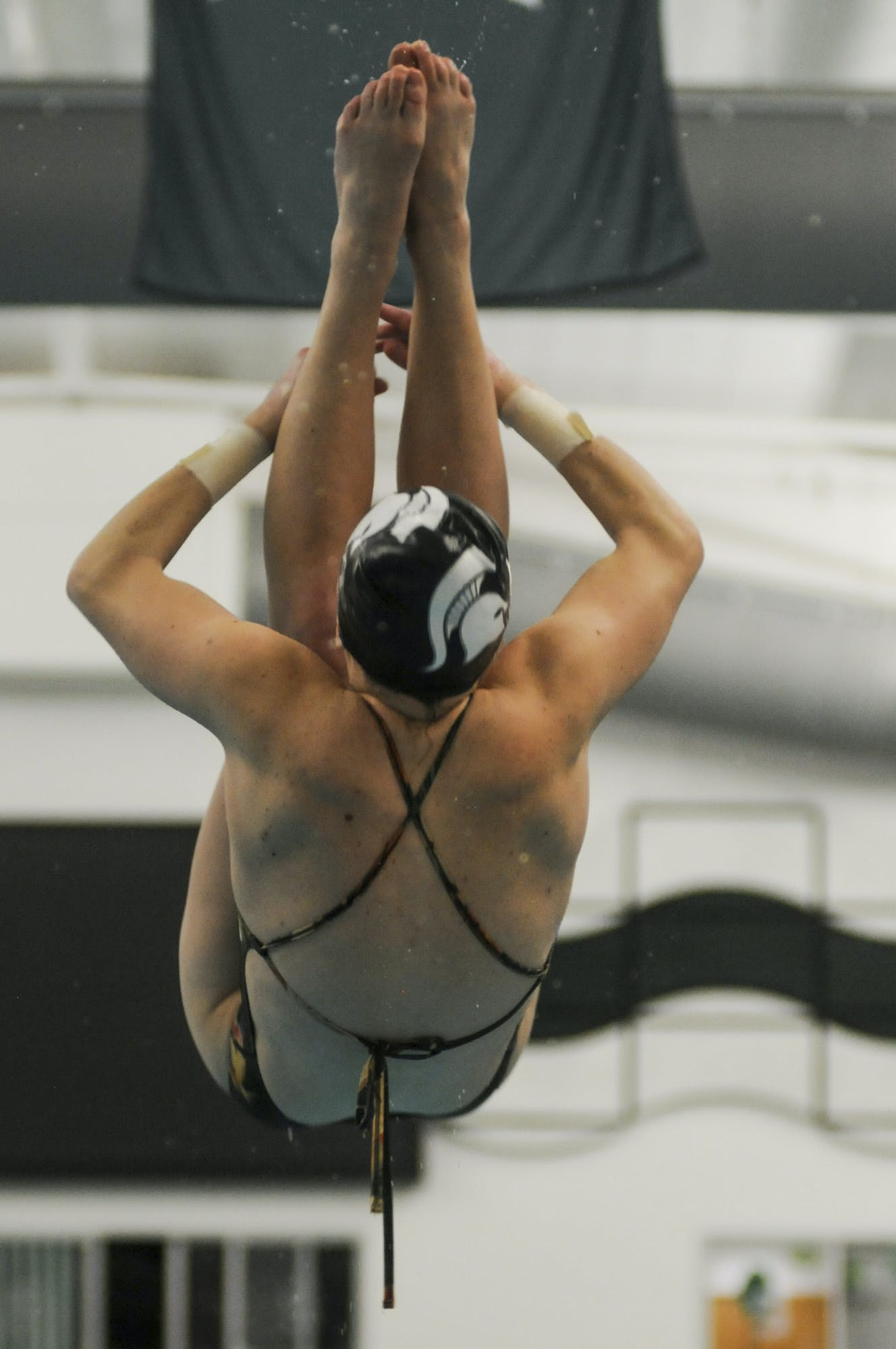 A person wearing a swimsuit and swim cap dives in mid-air, with their legs straight but tucked toward their body over their head.