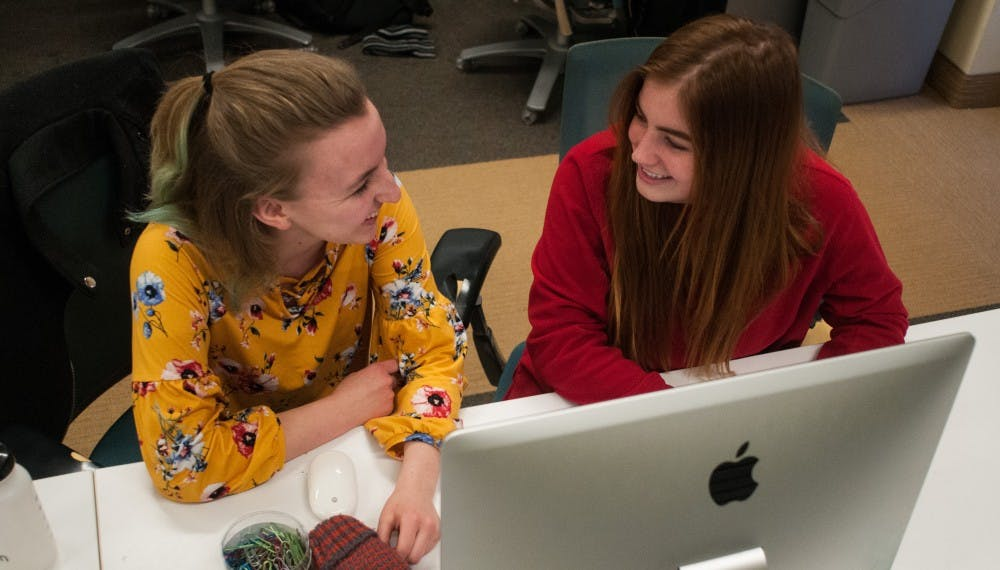 Campus reporter Claire Moore, left, and cops and courts reporter Anna Nichols, right, laugh at a desk at the State News office on Feb. 13, 2019.