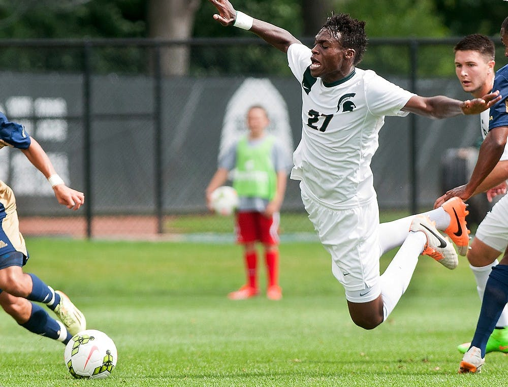 <p>Senior midfielder Fatai Alashe takes a fall while pushing through Florida International midfielder Donald Tomlinson Aug. 31, 2014, at DeMartin Soccer Stadium at Old College Field. The Spartans defeated the Panthers, 3-0. Raymond Williams/The State News</p>