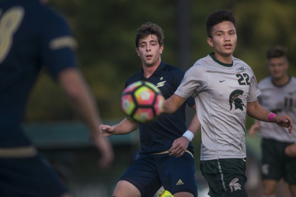 <p>Midfielder Ken Krolicki (22) attempts to block Akron midfielder Pau Belana (13) on a pass during the first half of the game on Oct. 11, 2016 at DeMartin Stadium at Old College Field. The Spartans defeated the Zips, 2-1.</p>