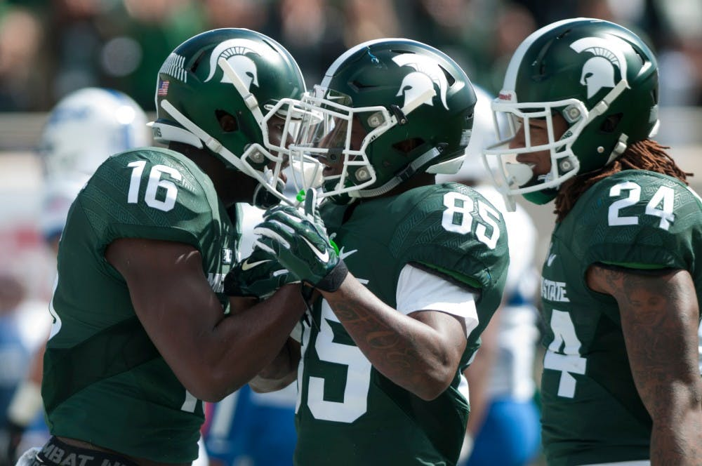 <p>Senior wide receiver Aaron Burbridge, 16, and senior wide receiver Macgarrett Kings Jr., 85, celebrate Burbridge's touchdown in the first half during the game against Air Force on Sept. 19, 2015 at Spartan Stadium. The Spartans defeated the Falcons, 35-21. </p>