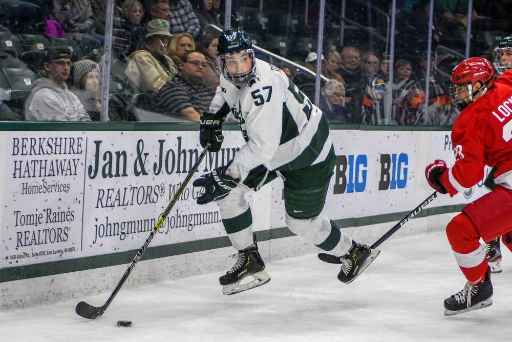 <p>Redshirt senior left defense Jerad Rosburg (57) takes the puck during the game against Cornell at Munn Ice Arena on Nov. 1, 2019. The Spartans were tied 1-1 with the Big Red at the end of the first period.</p>