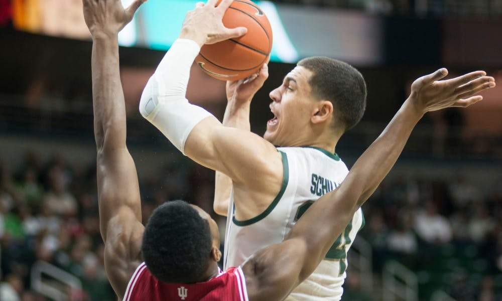 Sophomore forward Gavin Schilling attempts a point over Indiana forward Emmitt Holt Jan. 5, 2015, during the game against Indiana at Breslin Center. The Spartans defeated the Hoosiers, 70-50. Erin Hampton/The State News
