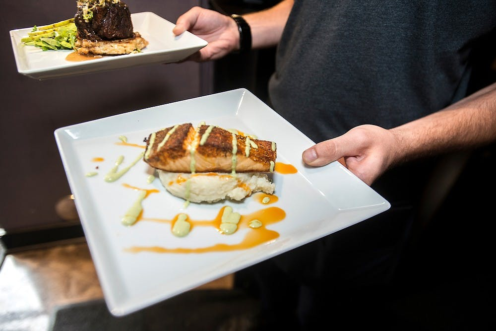 <p>Alumnus and East Lansing resident Seth Zundel serves food July, 30, 2014, at Black Cat Bistro in East Lansing. Zundel graduated with a degree in english in May, 2013 and is currently a server at Black Cat Bistro. Corey Damocles/The State News </p>