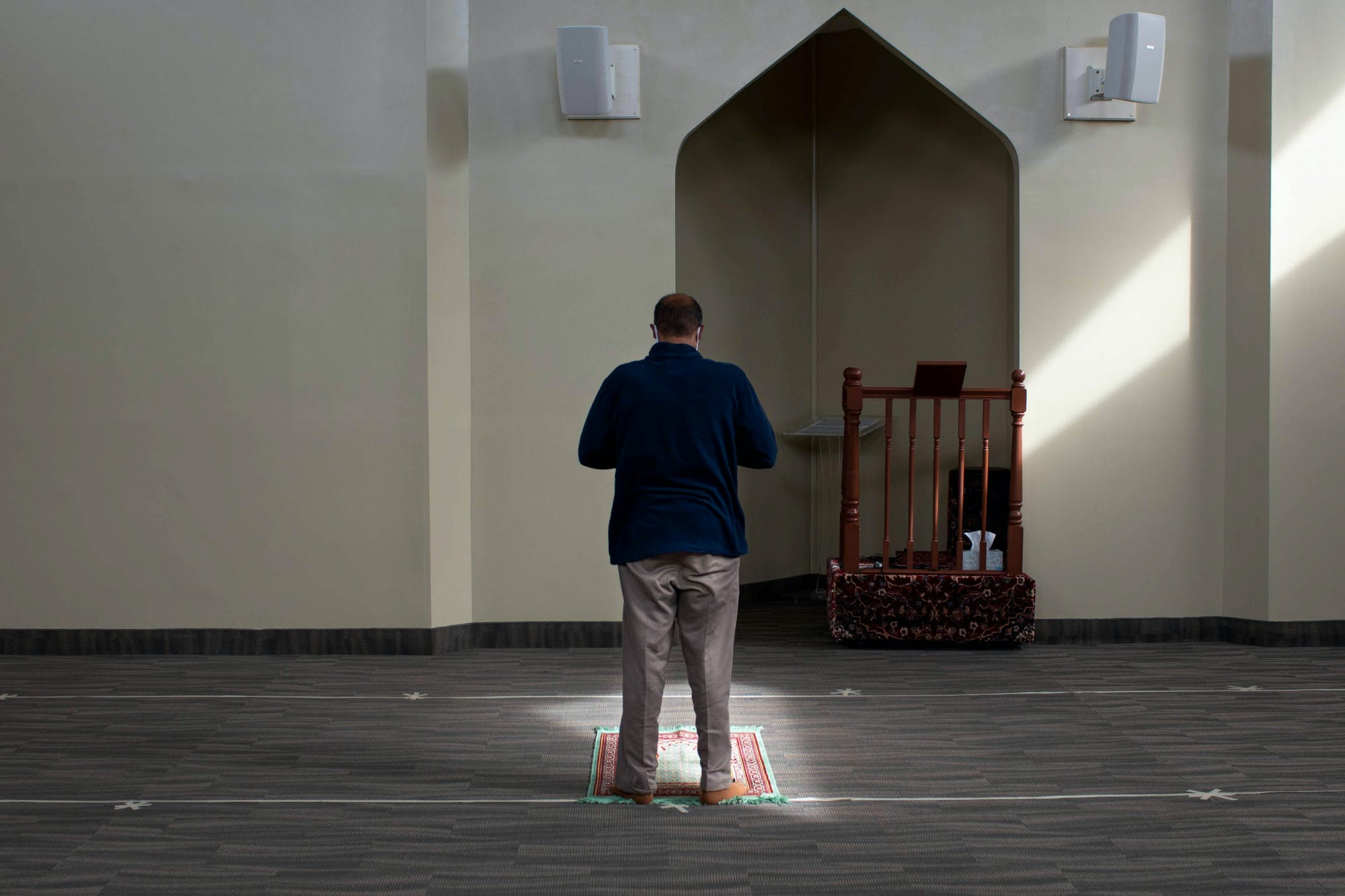 A man wearing a blue shirt, slacks and no shoes stands on a prayer rug. There are pieces of tape on the ground about six feet apart.
