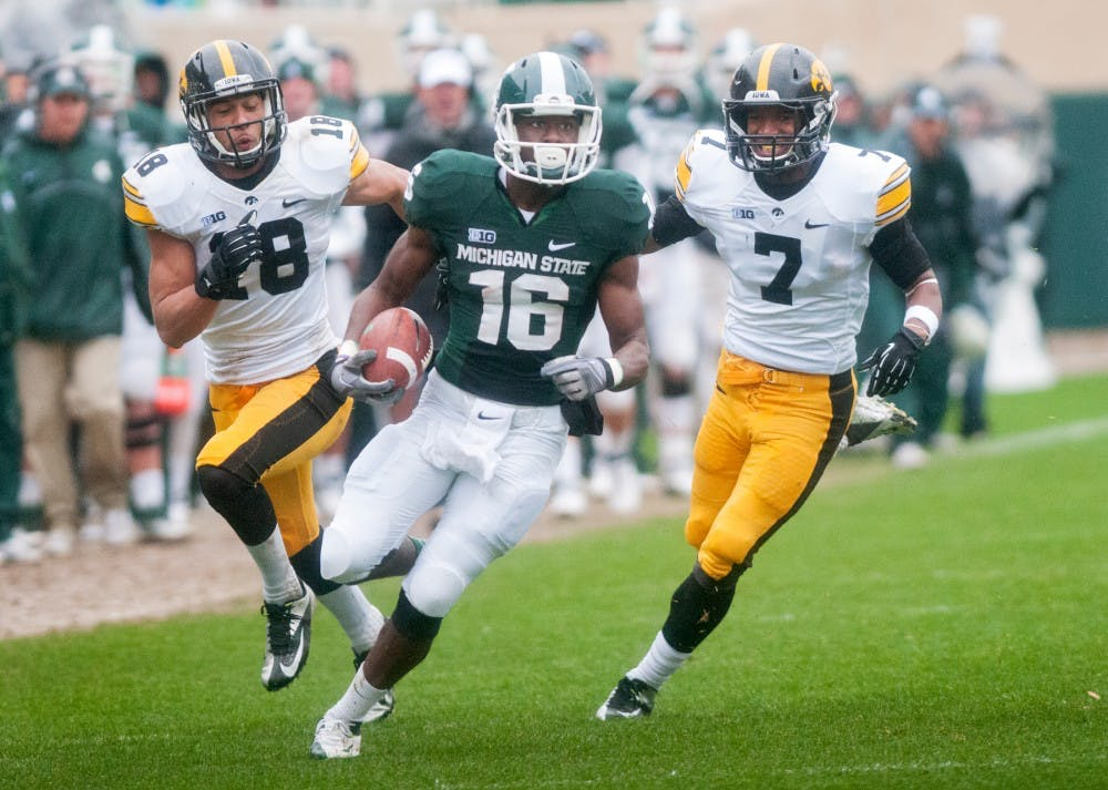 <p>Then-freshman wide receiver Aaron Burbridge runs from Iowa defensive backs Micah Hyde, left, and Sean Draper. Burbridge contributed 89 yards in the Spartans' 19-16 loss to the Iowa Hawkeyes. James Ristau/The State News</p>