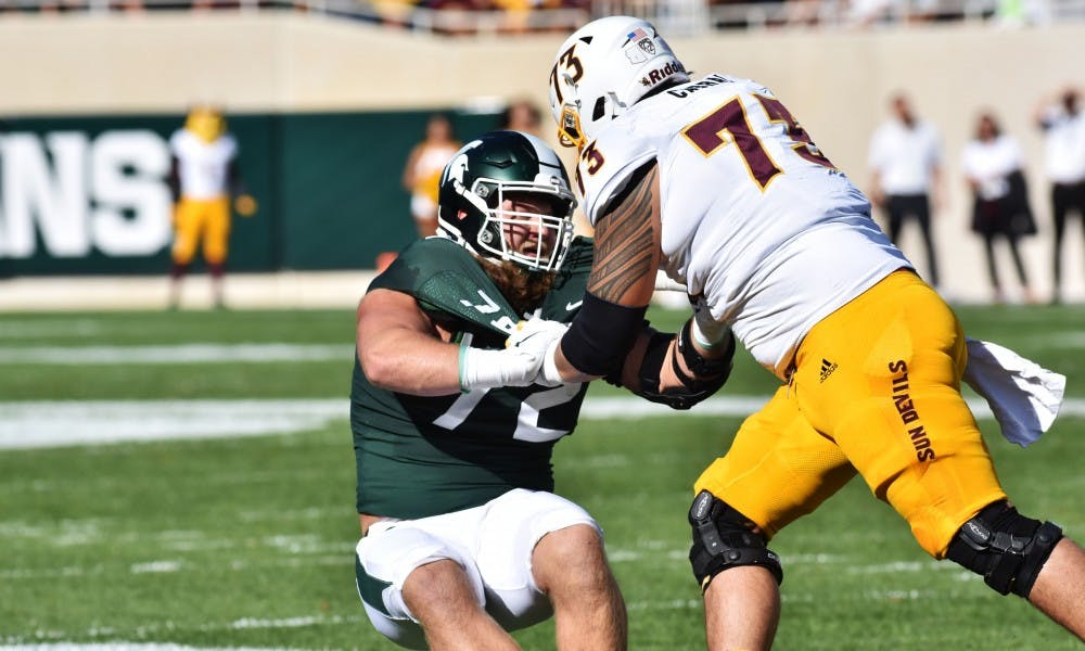 <p>Senior defensive tackle Mike Panasiuk (72) defends his teammates from an Arizona State left tackle. The Spartans fell to the Sun Devils 10-7 at Spartan Stadium on Sept. 14, 2019.</p>