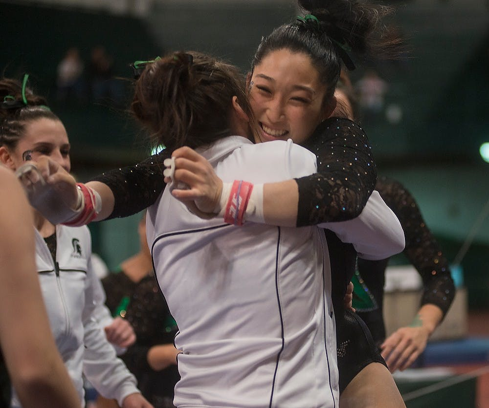 <p>Then-junior Lisa Burt hugs her teammates Feb. 13, 2015, after her performance on the bars at the women's gymnastics meet against Michigan. The State News File Photo</p>