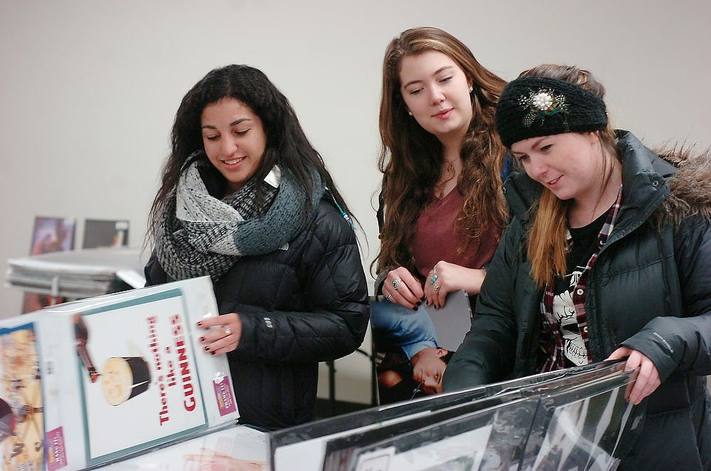 <p>From left, hospitality business sophomore Anna Margosian, special education sophomore Christina Connolly, and nursing junior Catie Ray look at posters Jan. 14, 2015, during the poster sale at the MSU Union. Jessica Steeley/The State News</p>