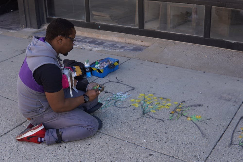 <p>During clean-up efforts June 1, Lansing artist Ryan Holmes painted flowers intertwining with the words of the message &quot;F--- 12&quot; that was left during a protest the night before. </p>