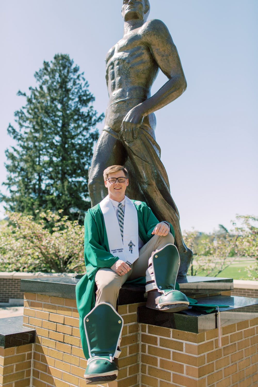 MSU alumni Joseph Hrabnicky poses in front of the Spartan Statue in his graduation gown and Sparty boots. Hrabnicky played Sparty since the second semester of his freshman year at MSU.