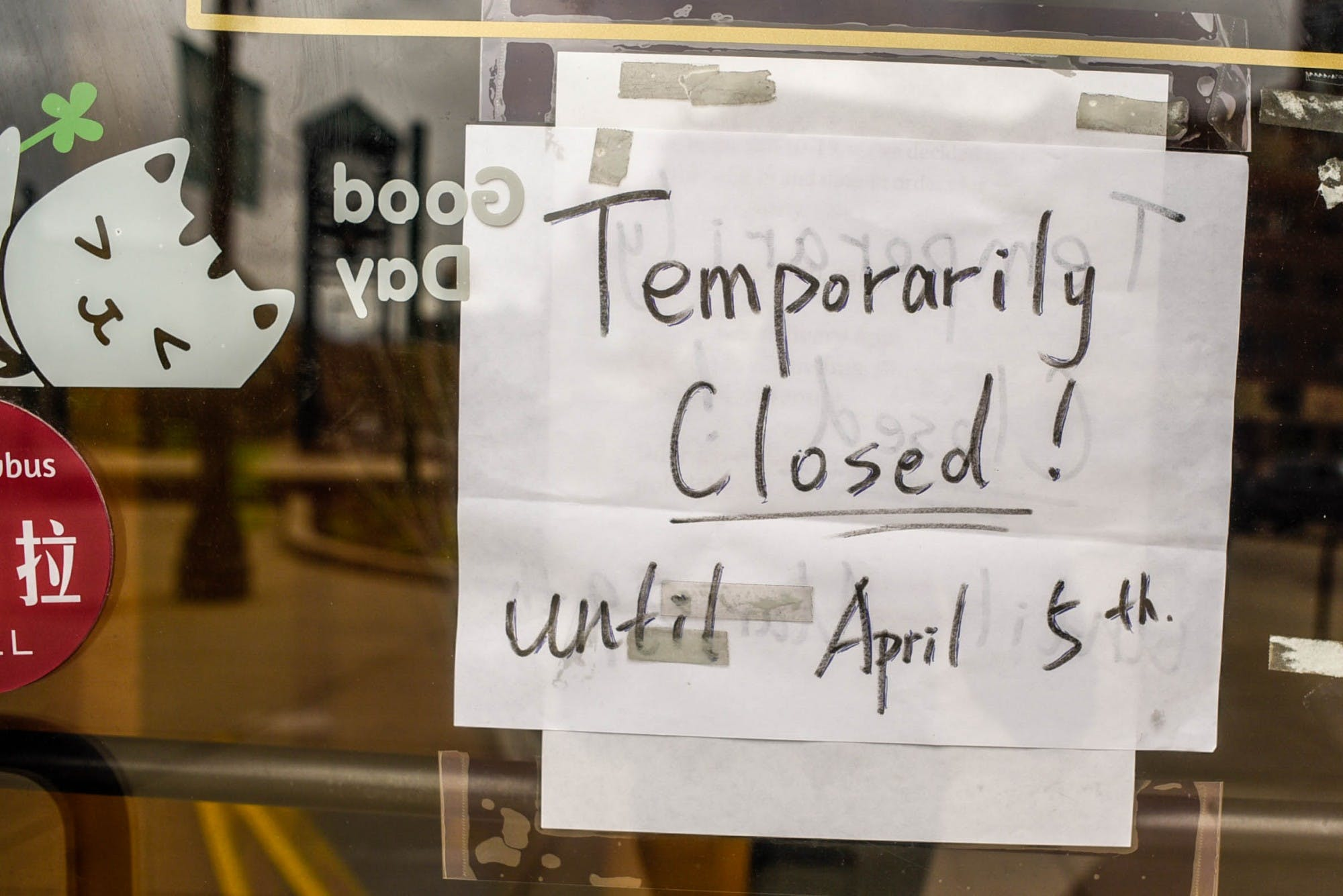 A piece of paper with a handwritten note that says 'Temporarily closed! Until April 5th' is taped to a window of a business.