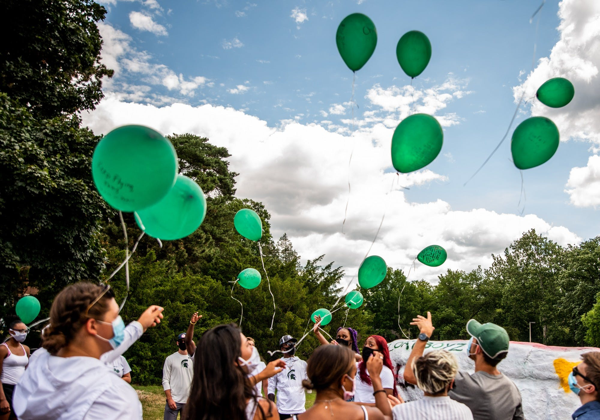 A group of people wearing face masks stand outside and release green balloons into the sky.