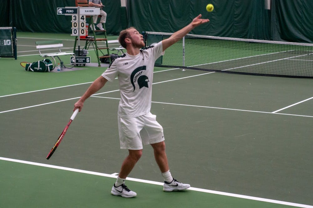 <p>Freshman Anthony Pero serves the ball during a singles match at the MSU Tennis Center on Jan. 12. Pero won his match.</p>