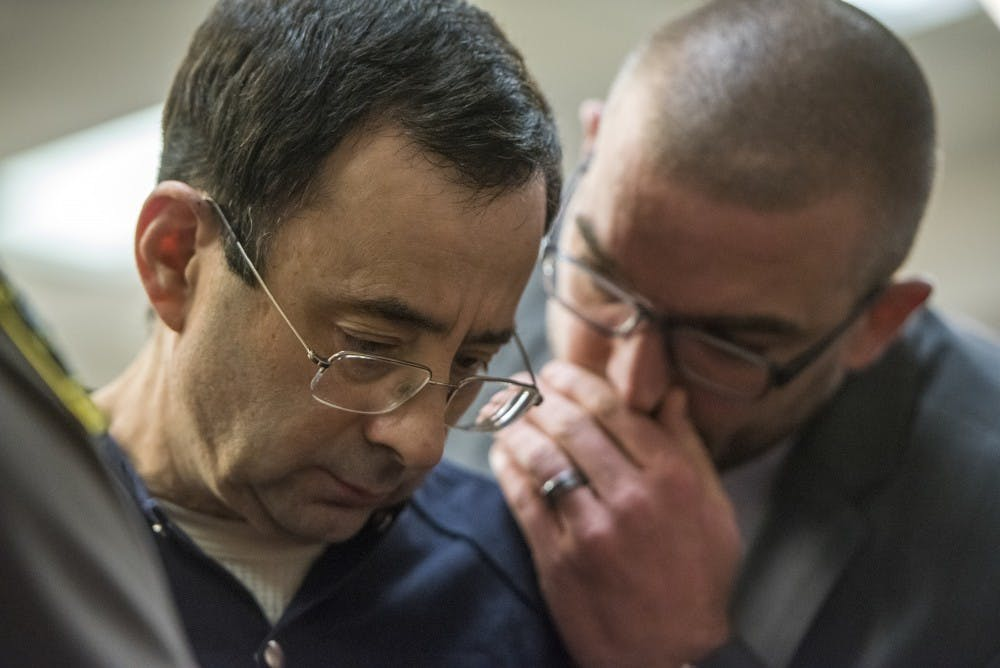 Ex-MSU and USA Gymnastics Dr. Larry Nassar talks with his attorney, Matt Newburg, on the fourth day of his sentencing on Jan. 19, 2018 at the Ingham County Circuit Court in Lansing. (Nic Antaya | The State News)