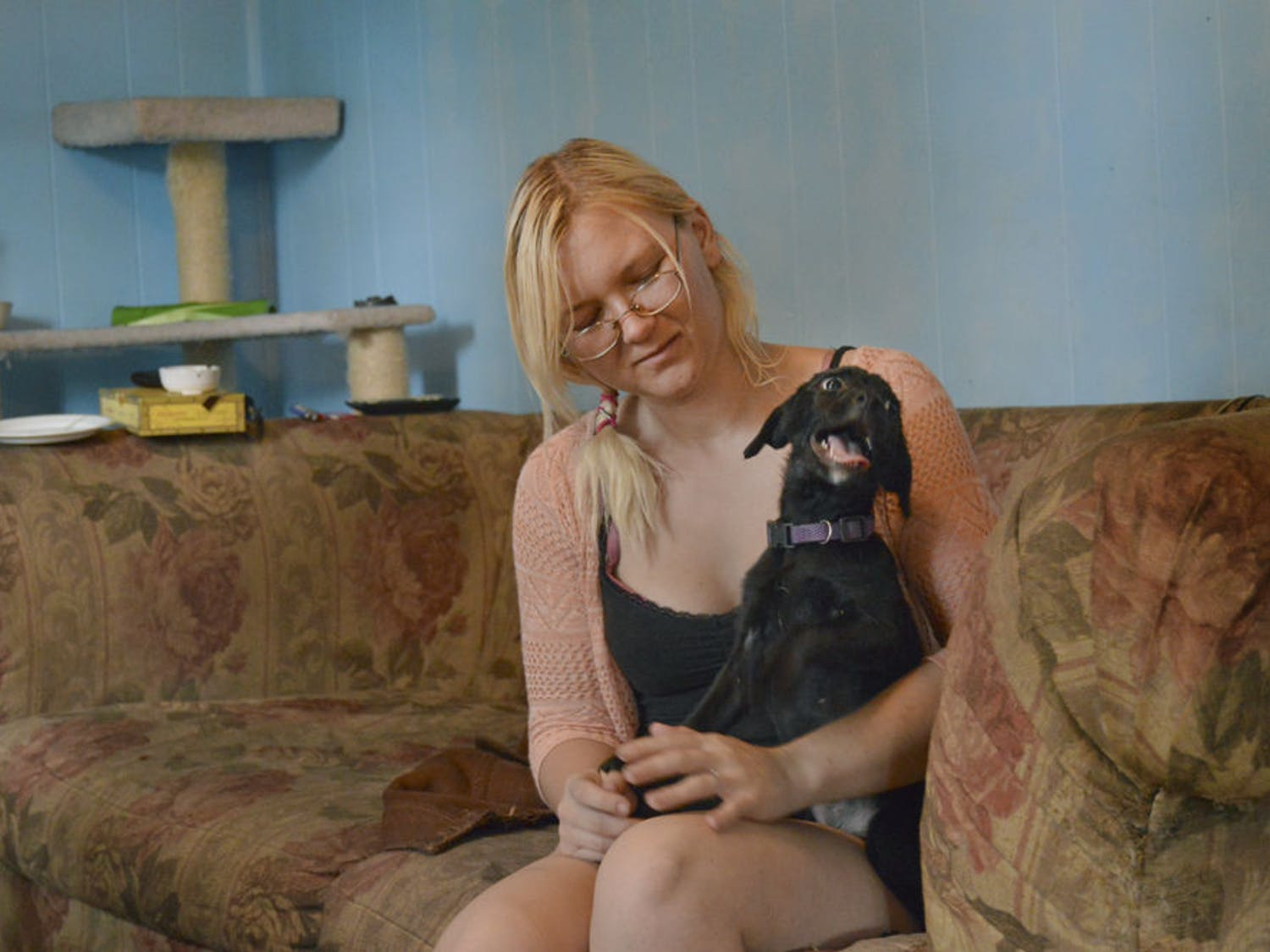 Rebecca Pardini plays in her home with Angel, a puppy she's taking care of for a friend. The 22-year-old was homeless for three years.