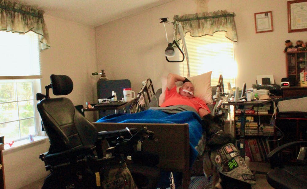 """<p><span id=""""docs-internal-guid-09f6de0e-644a-e69f-f702-1e6c965ae0d6""""><span>Michael Gaither, a U.S. Army veteran suffering from multiple sclerosis, lays in bed with his service dog, Honey, by his side. Both are fighting terminal illnesses and need constant medical treatments.</span></span></p>"""