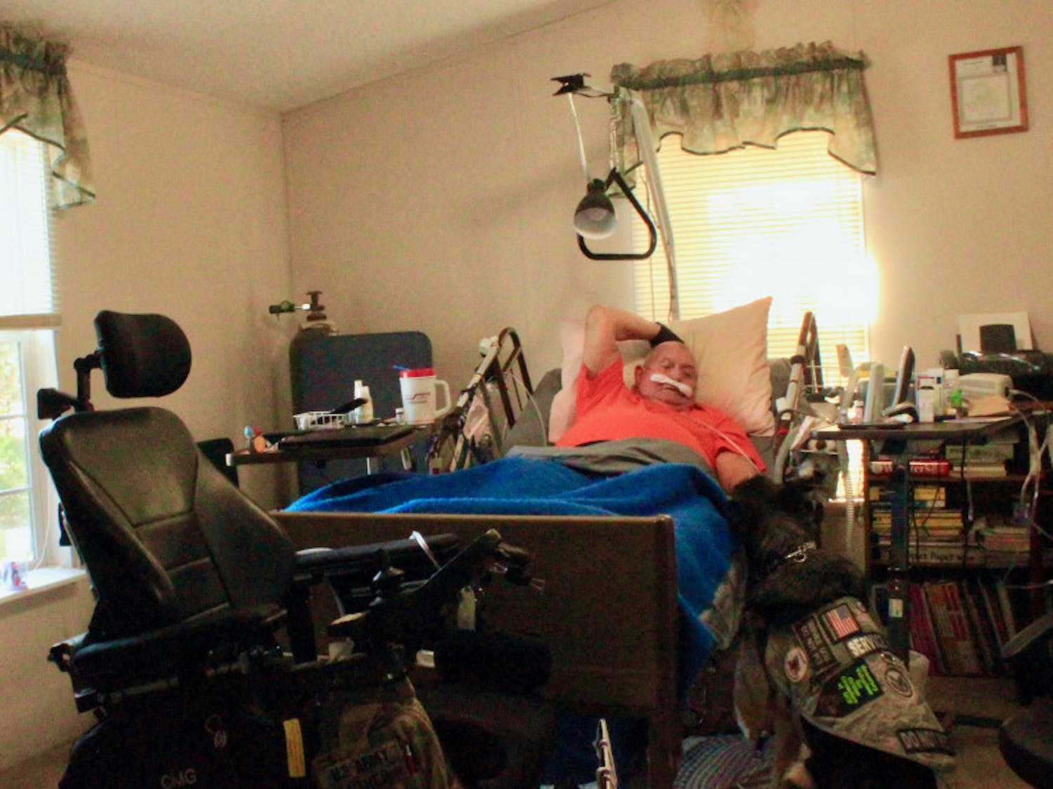 Michael Gaither, a U.S. Army veteran suffering from multiple sclerosis, lays in bed with his service dog, Honey, by his side. Both are fighting terminal illnesses and need constant medical treatments.