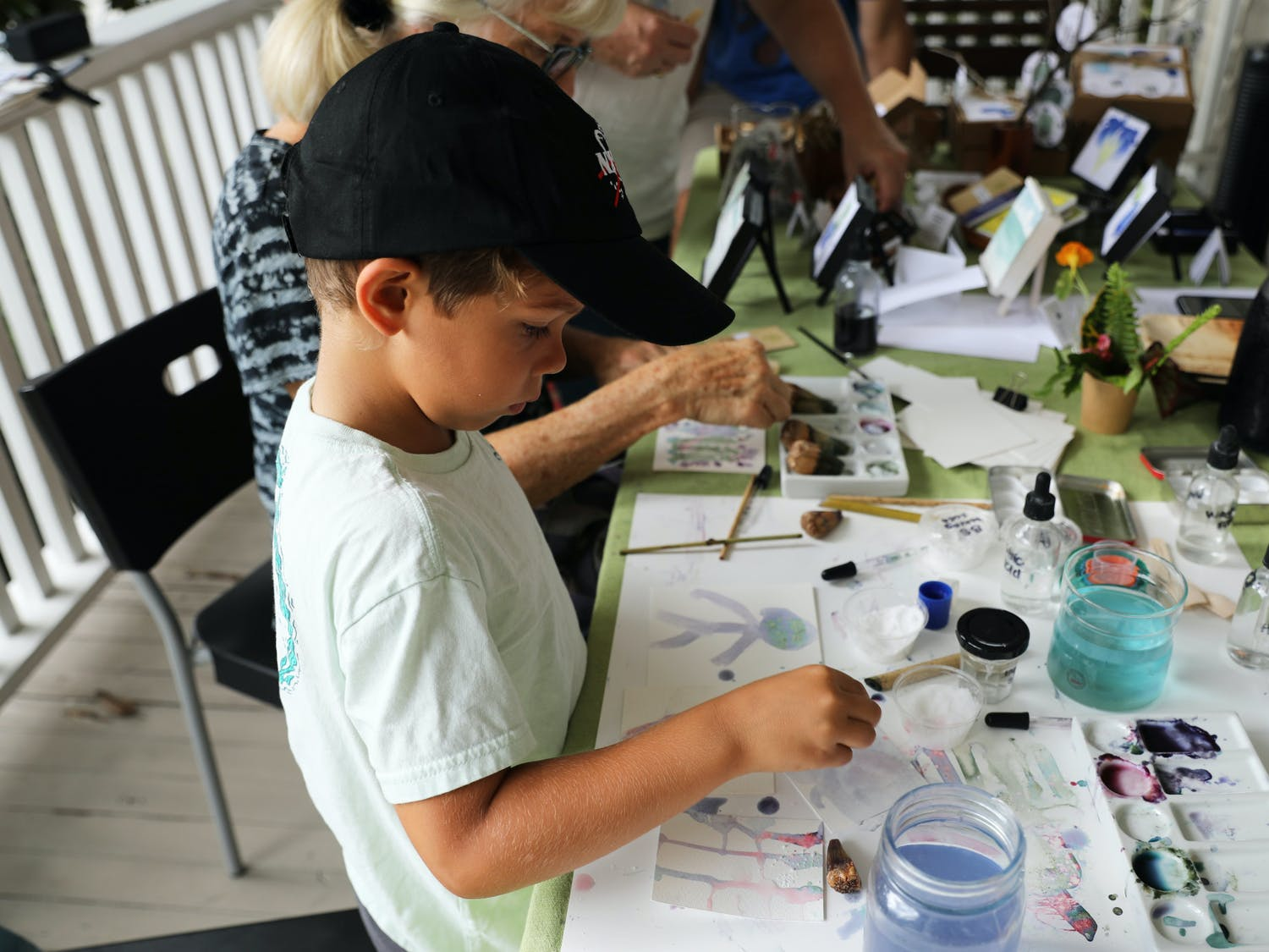 Dylan Perez, 6, uses blue butterfly flower pigment to paint on reusable paper at an eco-art event on Saturday, June 12, 2021.