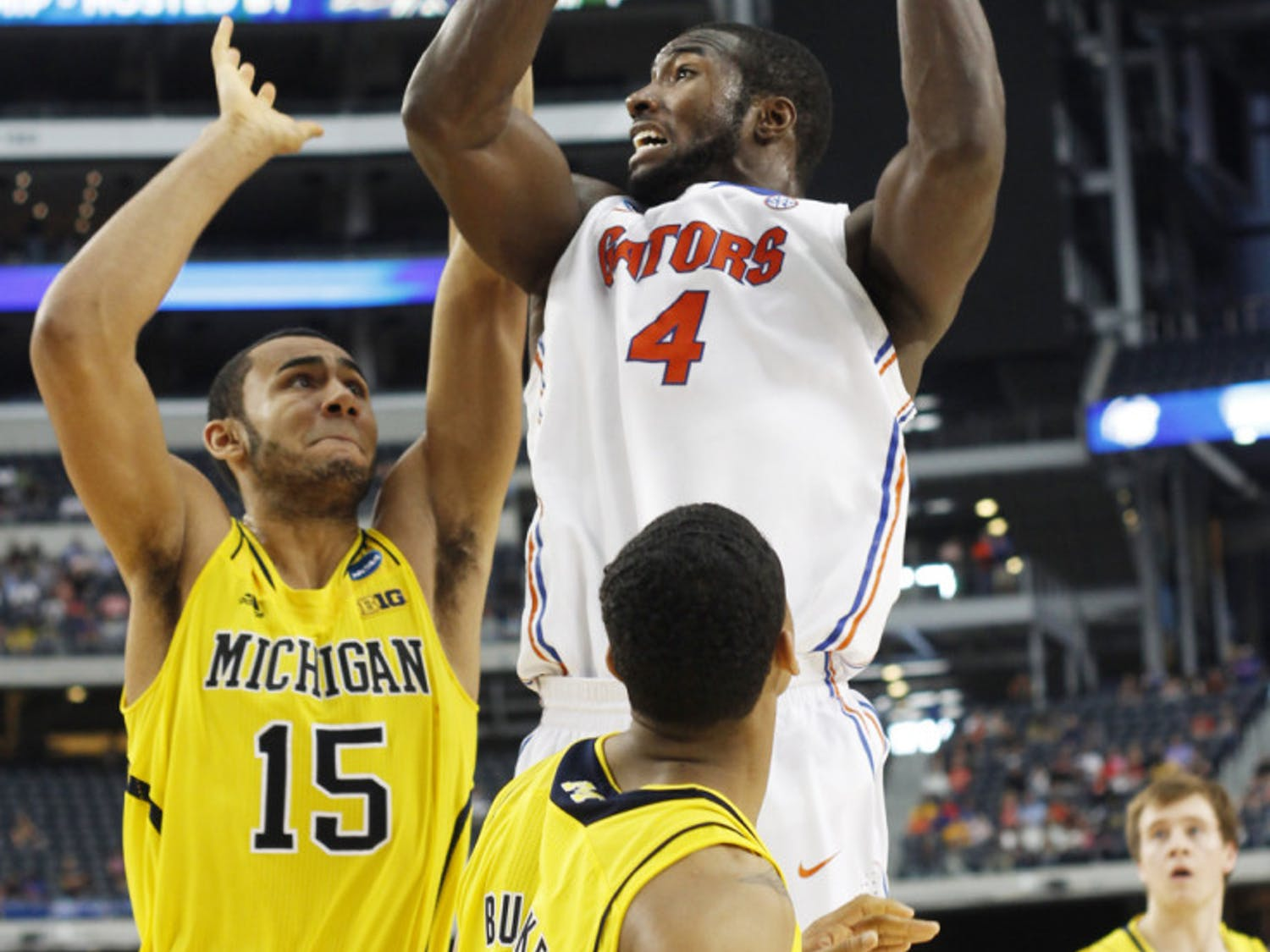 Junior center Patric Young (4) attempts a shot during Florida's 79-59 loss to Michigan in the Elite Eight on Sunday at Cowboys Stadium in Arlington, Texas.