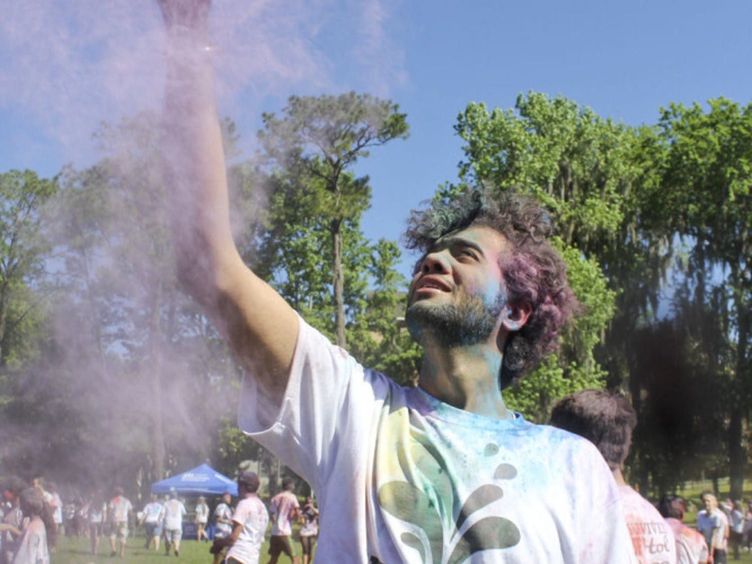 Deepanshu Soni, an information systems and operations management senior, flings colored powder in the air on Hume Field on Sunday. The 23-year-old threw the powder as part of UF Holi, a traditional Indian holiday that celebrates the coming of spring.
