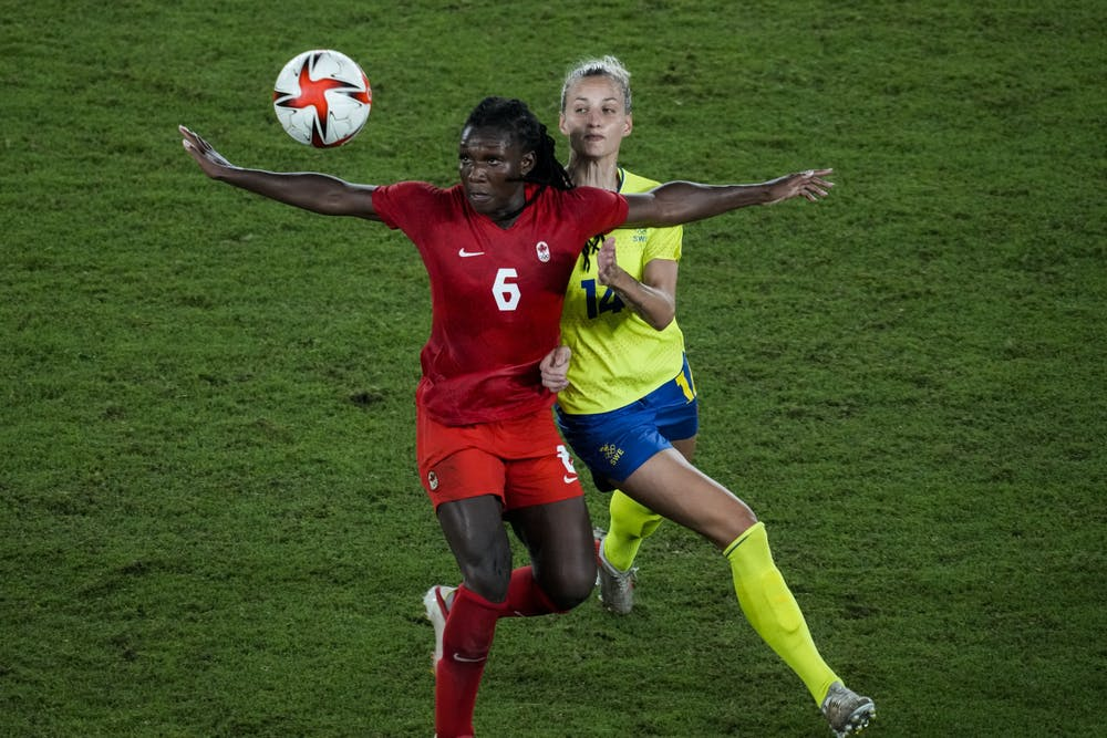 Canada's Deanne Rose duels for the ball with Sweden's Nathalie Bjorn during the women's final soccer match at the 2020 Summer Olympics, Friday, Aug. 6, 2021, in Yokohama, Japan. (AP Photo/Kiichiro Sato)