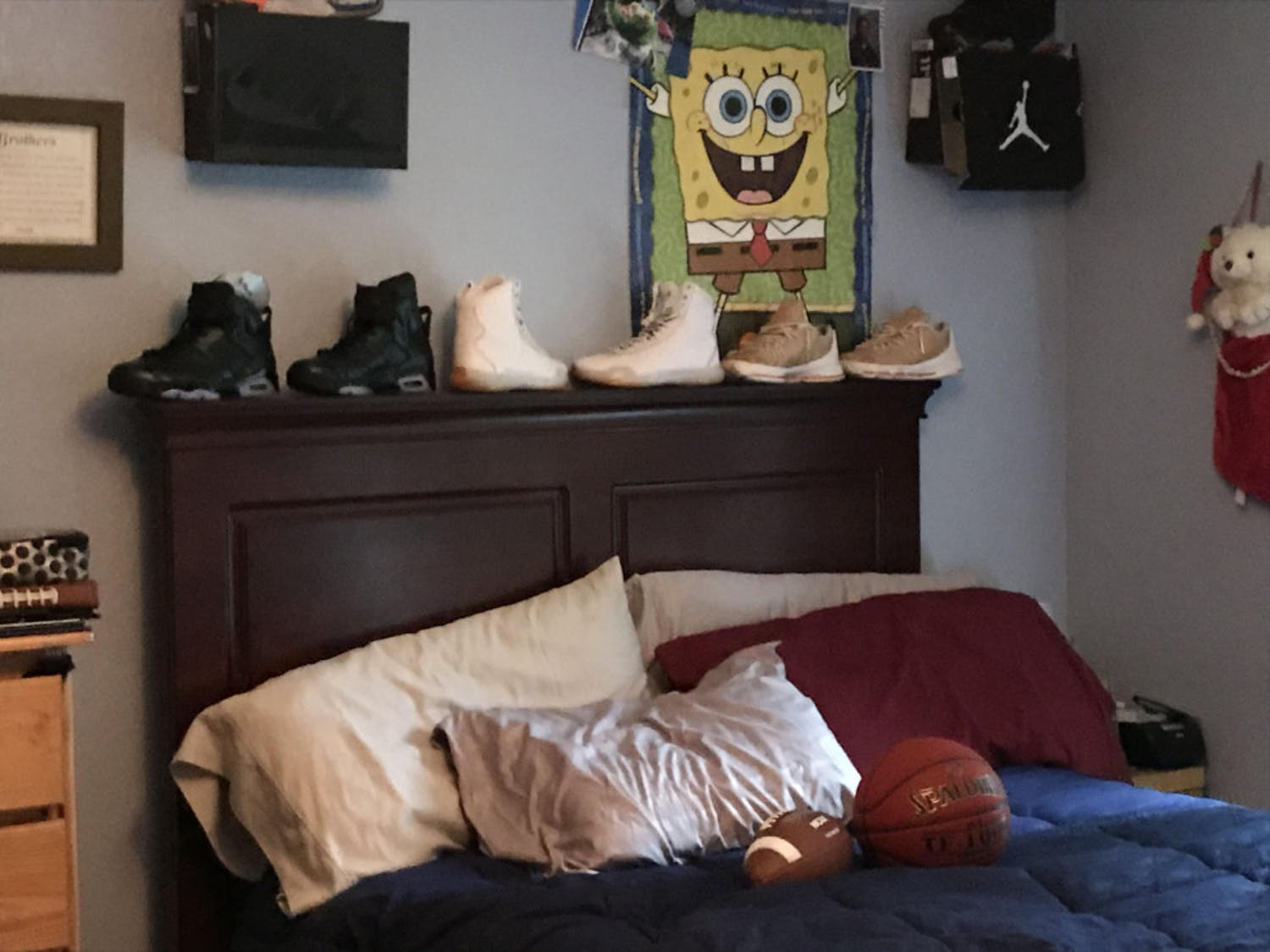 Sean's family keeps his bed made, his shoes on the headboard and his Spongebob Squarepants poster on the wall. Sean's Mario Kart backpack and some video games decorate the floor nearby.