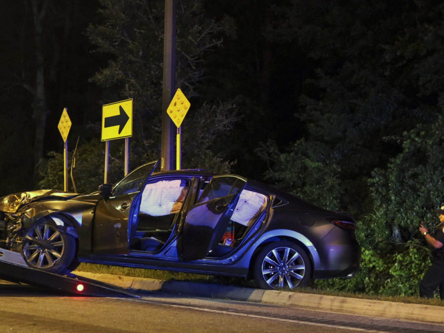 Gainesville Police Officer J. Allen inspects the crashed car Monday night.