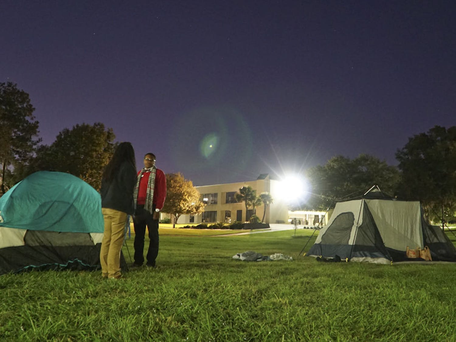 """Clarinda Choice (left), a 29-year-old Santa Fe student leadership and activity specialist, and Jacobi Bedenfield, a 19-year-old Santa Fe agriculture freshman, chat under Santa Fe's """"Oak Grove"""" late Nov. 23, 2015. Choice and Bedenfield were two of the five participants raising awareness for homelessness by camping overnight at the college."""