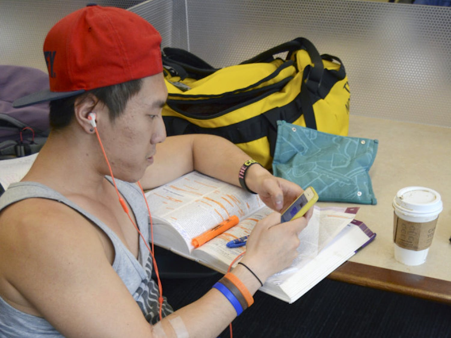 Thomas Sit, a 24-year-old UF public health graduate student, takes a break from his work to use his smartphone in Library West on Sunday. Sit said he probably accessed the internet more on his phone than his laptop, mainly because the phone was more convenient for him.