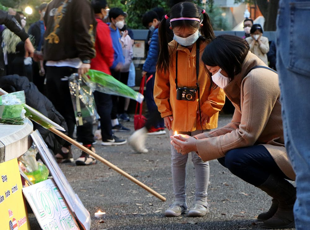 <p>Iris Wang, 6, (left) watches Minmin Jin, 43, a Gainesville resident (right), light a candle in front of Turlington Plaza Saturday, March 20, 2021. The two stood with a large crowd commemorating the tragedy in Atlanta and calling attention to racism against Asian Americans.</p>