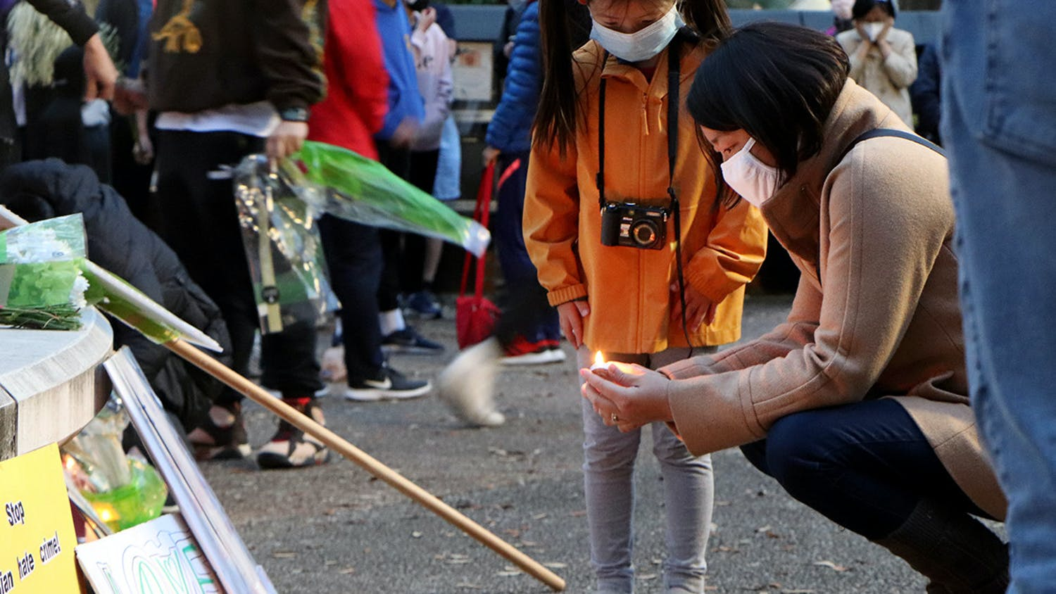 Iris Wang, 6, (left) watches Minmin Jin, 43, a Gainesville resident (right), light a candle in front of Turlington Plaza Saturday, March 20, 2021. The two stood with a large crowd commemorating the tragedy in Atlanta and calling attention to racism against Asian Americans.