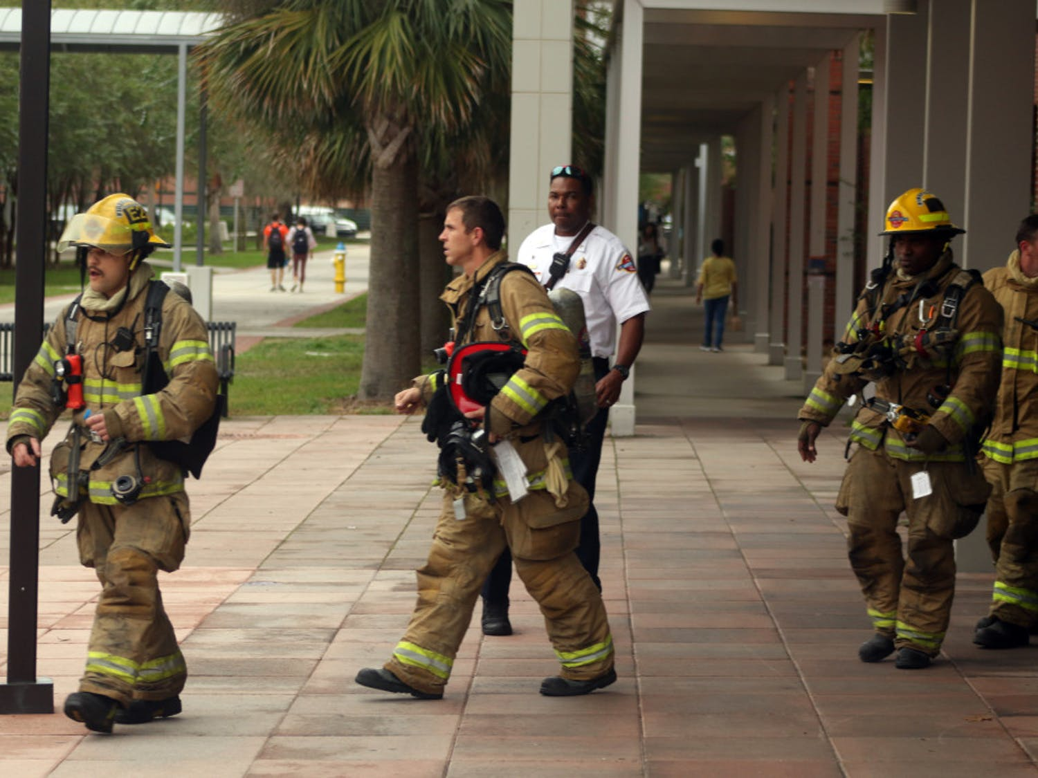 Gainesville Fire Rescue firefighters come out of the Biomedical Sciences Building in bunker gear after assessing the chemical spill on Monday, Nov. 5, 2018. The spill was contained within the fume hood and the hazmat team determined that the room was safe.