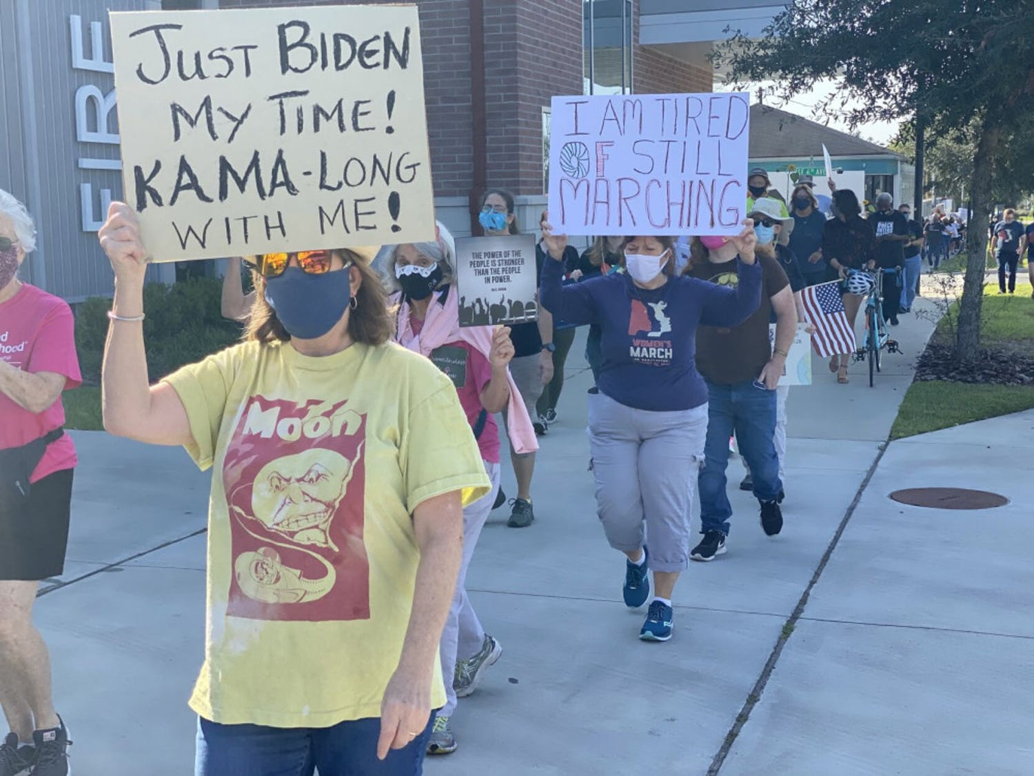 "Marchers carry signs with messages such as ""Just Biden my time! Kama-long with me!"" and ""I am tired of still marching"" in support of Democratic presidential nominee Joe Biden and vice presidential nominee Kamala Harris."