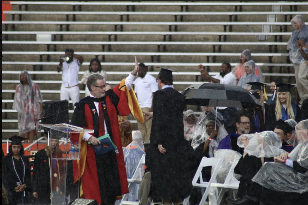 """<div><span style=""""color: #000000;"""">College of Liberal Arts and Sciences Dean, David Richardson, gestures to pause the commencement ceremony. Richardson announced the ceremony would be delayed by 30 minutes, but the ceremony was later moved to an inside</span></div><div><span style=""""color: #000000;"""">hallway of the stadium.</span></div>"""