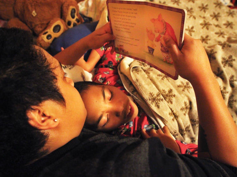 Joel Ratovoson reads a bedtime story to Daniel Ratovoson on Nov. 27.