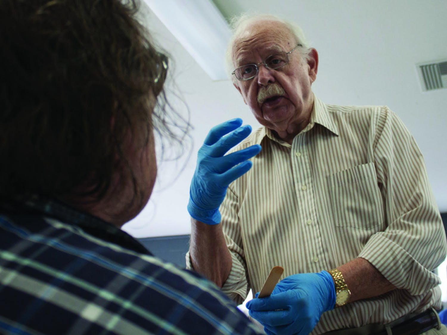 Dr. Fred West examines a patient, who complains of pain in the mouth after having his teeth removed, at an open wound clinic in Grace Marketplace on March 27.